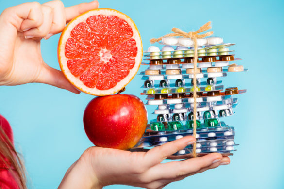 Health and balanced diet concept. Choice between two sources of vitamins - pills or fruits. Closeup female hand holding stack of drugs apple and grapefruit on blue.